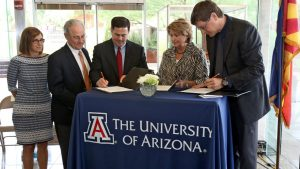 Gov. Doug Ducey, third left, signs an agreement with University of Arizona President Ann Weaver, second right, and Brian McClendon, the vice president for Uber which will allow them to the test and do research on driverless technology in the Tucson area. (A.E. Araiza/Arizona Daily Star via AP)